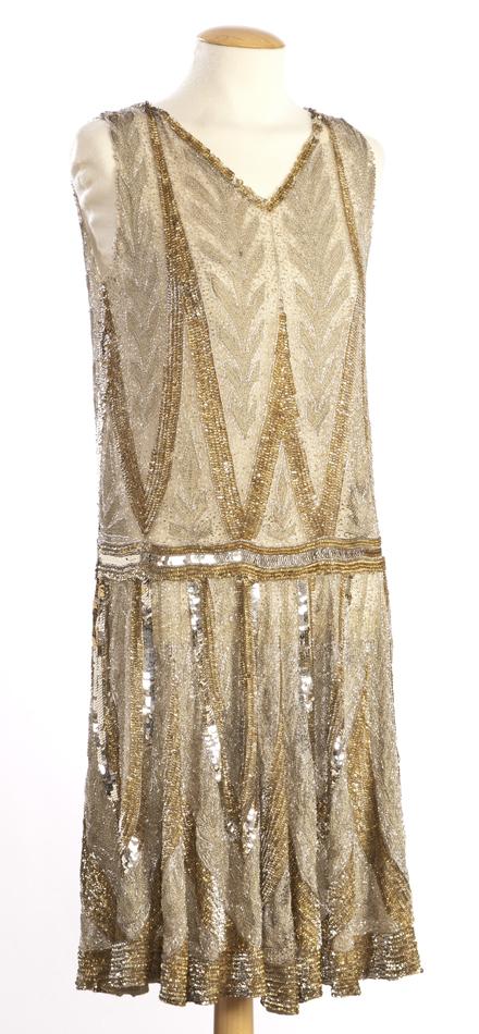 Vestit de tul beix, amb brodat de fil metàl·lic, lluentons or i plata i granadura de vidre