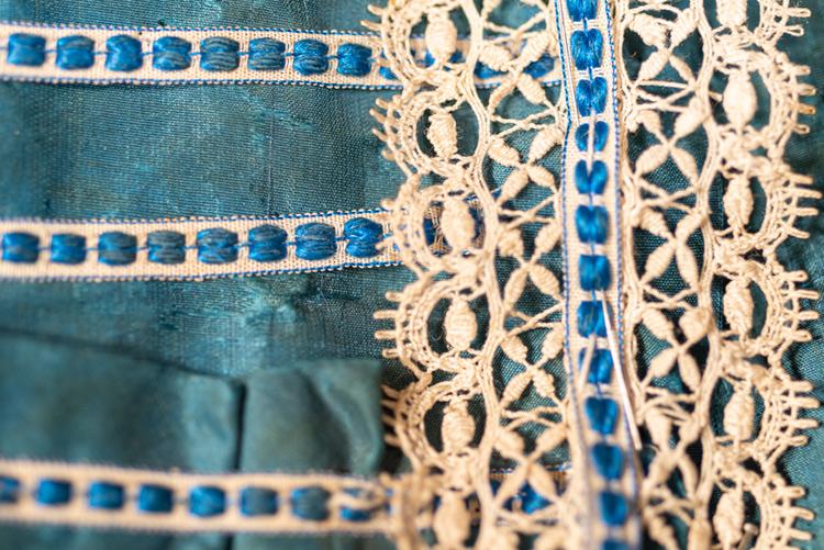 Imatge nina maniquí. Detall de les puntes al coixí i la passamaneria que decora el vestit.